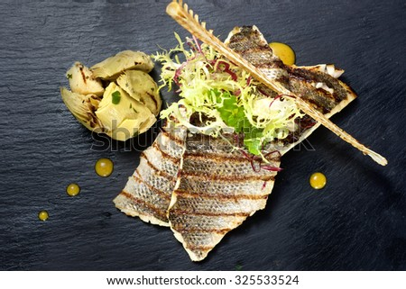 Sea bass fillet dish on black stone plate from top view - stock photo