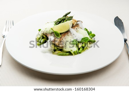 Sea bass fillet with asparagus infused with sauce foam - stock photo
