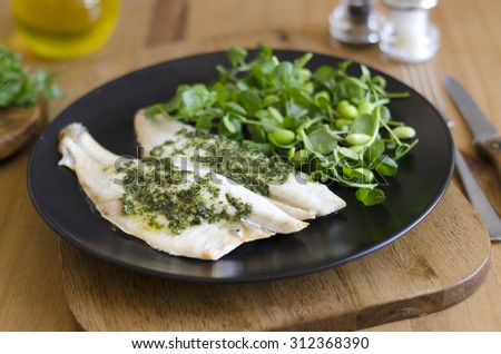 Sea bass fillets with a rocket and pesto butter - stock photo