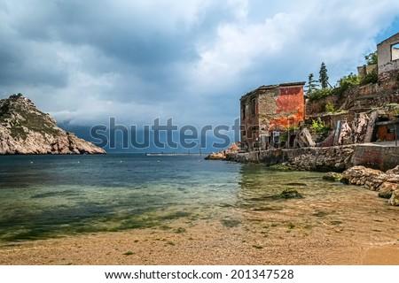 Sea bay and ruins of house in cloudy weather in Balaklava, Sebastopol, Crimea - stock photo