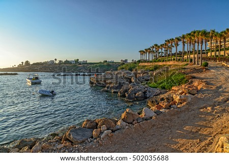 Sea bay with boats and resort area on coast in sunset light