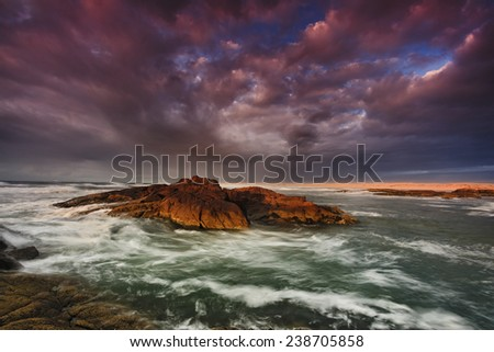 sea beach at sunrise with strong storm, wind, thunder dark clouds and dangerous waves - stock photo