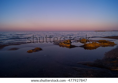 Sea, beach at sunset with red and blue sky