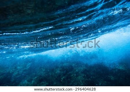 Sea bottom with blue water wave splash background - stock photo