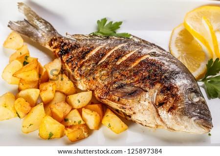 Sea bream fish with potato on white plate close-up - stock photo
