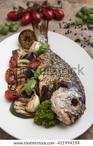 Sea bream on a plate with baked vegetables in company of fresh herbs and spices.