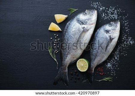Sea breams with seasonings on a black wooden surface, above view