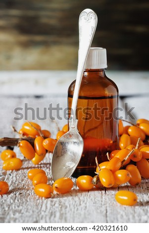 Sea buckthorn oil in a bottle and fresh sea buckthorn on a white wooden background. Alternative medicine.  Selective focus - stock photo