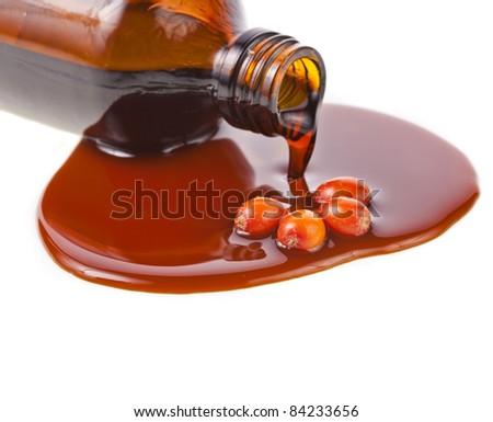 sea-buckthorn oil spilling from bottle  isolated on white - stock photo