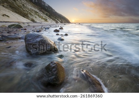 sea cliff and beach lit by the setting sun - stock photo