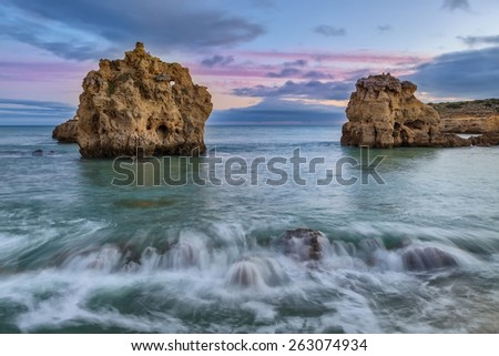 Sea cliffs in the sea into the sunset. Blurred waves. - stock photo