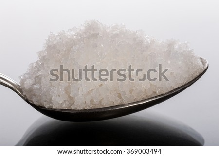 Sea coarse salt in spoon close-up. Side view. - stock photo