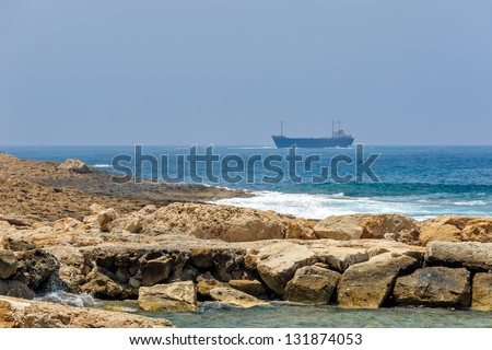 Sea coast and cargo ships on horizon