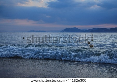 Sea coast in blue tones of sunset, with small waves and row of floating buoys. Mountains in layers in background. - stock photo