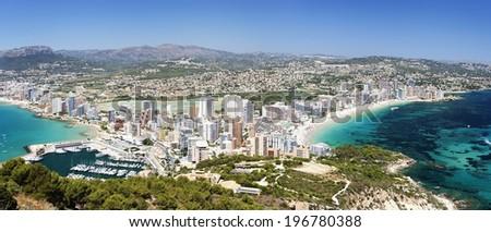 Sea coast with people bathing on the background of the sunny city (Coastline Costa Brava - Spain) - stock photo