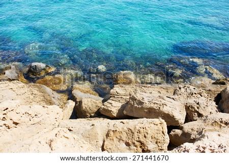 Sea coast with rocks, transparent blue shallow water. - stock photo