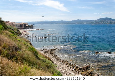 Sea coast with view on mountains and buildings - stock photo