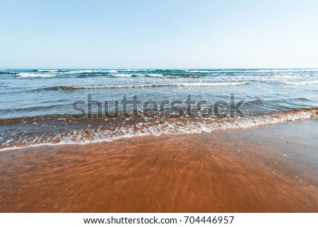 Sea coast with waves, golden sand