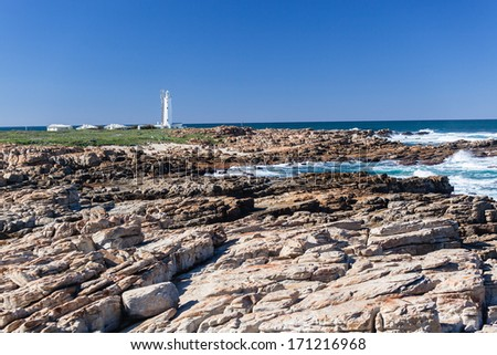 Sea Coastline Rocks Lighthouse Sea coastline rocky outcrop shelfs with distant white lighthouse warning passing maritime ship crews of shoreline dangers. - stock photo