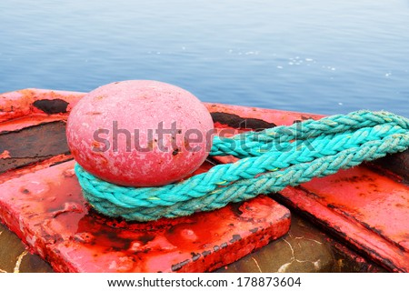 Sea concept : red mooring bollard for very large boat over ocean - stock photo