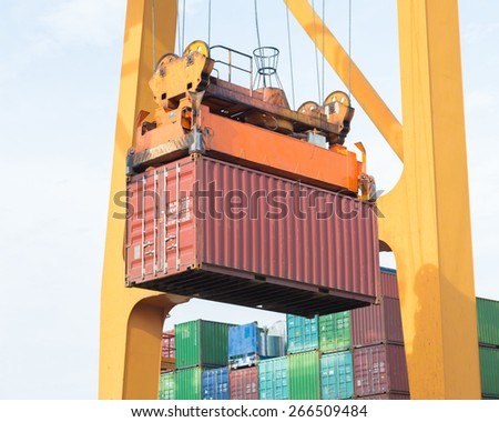 Sea container lifted by a harbor crane at ship yard - stock photo