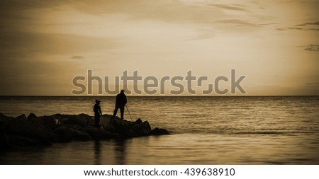sea dawn with fishermen - stock photo