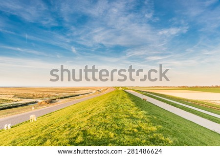 Sea dike under a blue sky in the north of Holland - stock photo