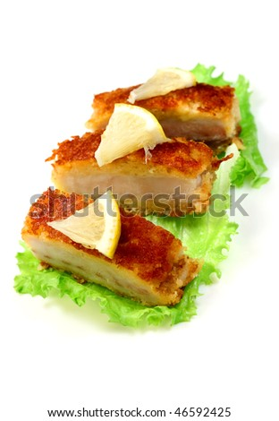 Sea food.  Roasted fish with lemon and lettuce on a plate