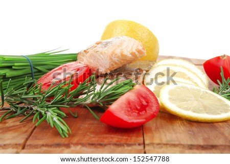 sea food : roasted pink salmon fillet with chinese onion, cherry tomatoes pieces, rosemary twigs and lemon on wooden board isolated over white background