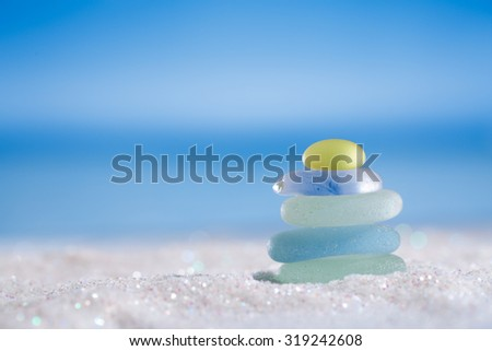 sea glass seaglass stone on glitter sand with ocean , beach and seascape, shallow dof