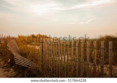Sea grass, sand dunes and barrier fence at sunset. - stock photo