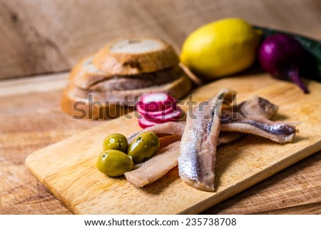 Sea herring with garnish on wooden plate - stock photo