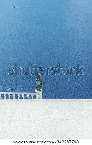 Sea horse from the metal and rock crystal adorn the terrace of a Greek house.Mediterranean sea on the backdrop.Minimalistic composition.Santorini (Thira) island.Cyclades.Greece.Europe. - stock photo