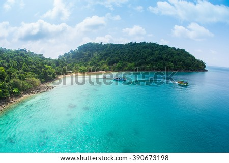Sea lagoon with cyan water,ferry boats and tropical trees - stock photo