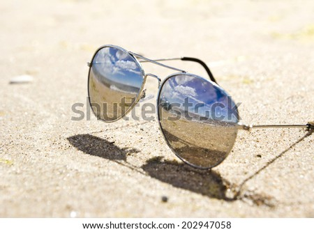 sea landscape reflecting in the sunglasses on the beach - stock photo