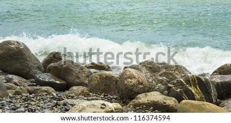 Sea landscape - stones on shore and waves with foam.