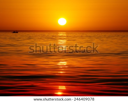 Sea landscape, vivid sunset. Calm sea. Silhouette of fishing vessel.