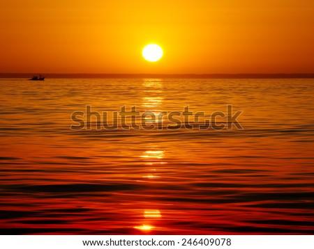 Sea landscape, vivid sunset. Calm sea. Silhouette of fishing vessel. - stock photo