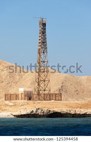 Sea Lighthouse on stony bare mountain under a clear blue sky - stock photo