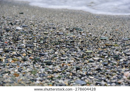 Sea multicolored pebbles, gravel beach in sunlight, selective focus, background - stock photo
