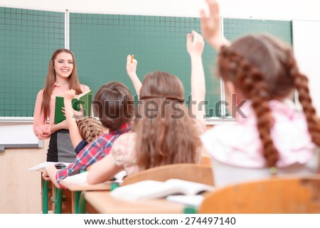 Sea of hands. Sea of raised hands of little pupils during classes and happy teacher. - stock photo