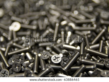 Sea of Screws Lots of silver colored screws. Selective focus. Shallow depth of field. Horizontal. - stock photo