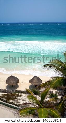 Sea Palm Beach umbrellas on the beach along the Caribbean Sea Mexico - stock photo