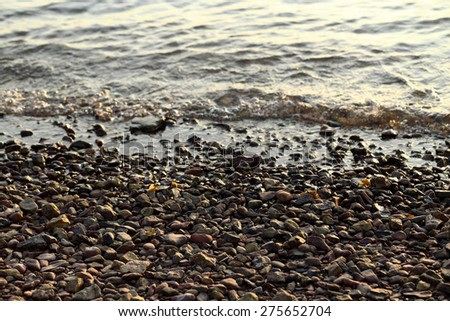 Sea pebble - gravel beach in sunlight, selective focus for background. - stock photo