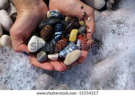 Sea pebbles in woman's hands - stock photo