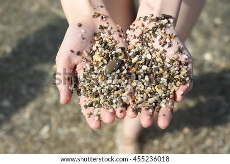 Sea pebbles on the palms - stock photo