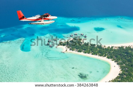 Sea plane flying above Maldives islands - stock photo