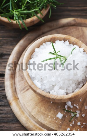 Sea salt and green rosemary in the wooden bowl, selective focus