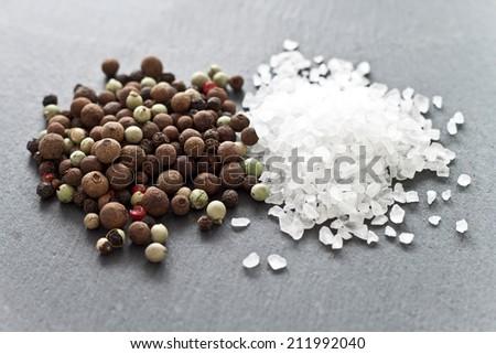 Sea salt and pepper heaps on a slate - stock photo