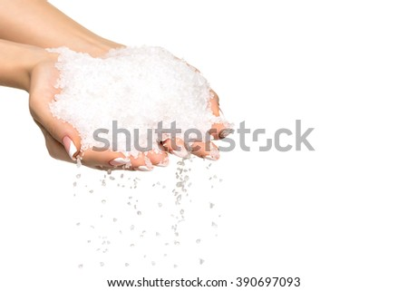 Sea salt crystals in women hand on white background